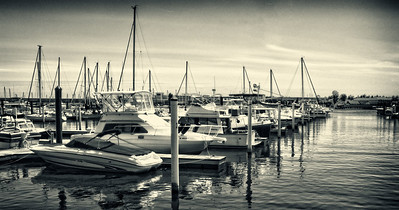 "My family and I took a trip to New Bern, NC recently. Though I had never been to that area, my mother and father had spent a day there on a vacation a year ago and she had been looking forward to going back. I was thinking it would be similar in ambience to a place like Wilmington, with places to eat down by the water. Strangely, the only place to eat by the water is a local HIlton, though there are rumors you can view the water from the roof of Captain Ratty's in town. My father and I wanted to go to the Captain Ratty's route, however, my mother decided she would rather eat at the hotel. That meant my father and I were outvoted. After the meal we took a walk down by the water and I took advantage of any docks that didn't have their ""keep out"" signs up.  This image is actually an HDR that I took with my zipshot tripod while standing just off one of the docks. I had liked the shot originally (I personally love the look of HDR water, especially having applying the Tonal Contrast Filter from Color Efex Pro), however, when taking multiple exposures manually (as I've said before, my camera doesn't do autobracketing for RAW files), it means that it takes about 20-30 seconds to fire off all my images. This was particularly problematic for me on this shot because it meant the boats were moving slightly in each image. In Photomatix, this meant that my final image had this little bit of autofocus / blurring around the boats and dock. It was hardly noticeable, but if you looked at the image for awhile, then your eyes would really start to correct it and you'd almost get a headache. Now, I don't pretend to be a photographic master by any stretch of the imagination, however, I know I don't want my images to give people headaches. Thankfully, the new Photoshop CS5 HDR processing's anti-ghosting capabilities fixed that problem and I was left with a shot that hopefully is not headache inducing.  [ Available at http://johnkivus.com/2010/05/16/harbor-view/ ]"